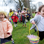 Excited kids running to collect eggs at the Easter Egg Hunt