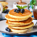 Stack of fluffy pancakes topped with blueberries