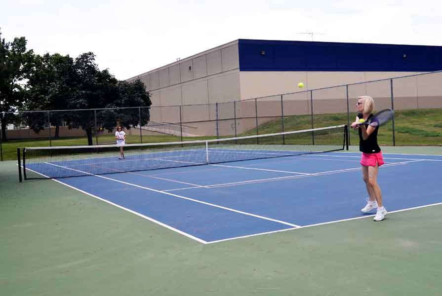 Woman playing tennis at Apel - Bacher Park